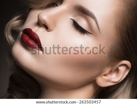 Beautiful blonde in a Hollywood manner with curls, red lips. Beauty face. Picture taken in the studio - stock photo