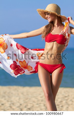 Beautiful blonde in a red bikini letting her sarong flow in the breeze at the ocean - stock photo