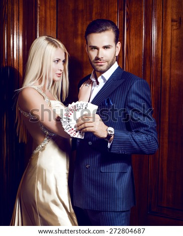 beautiful blonde in amazing dress hugs man with cards in casino - stock photo