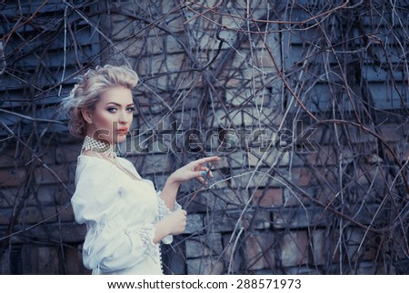 Beautiful blonde in an old white satin dress, a mysterious atmosphere, loneliness, mystery - stock photo