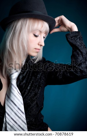 beautiful blonde in black clothes and men's necktie and a hat - stock photo