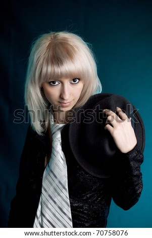 beautiful blonde in black clothes and men's tie, hat in hand - stock photo