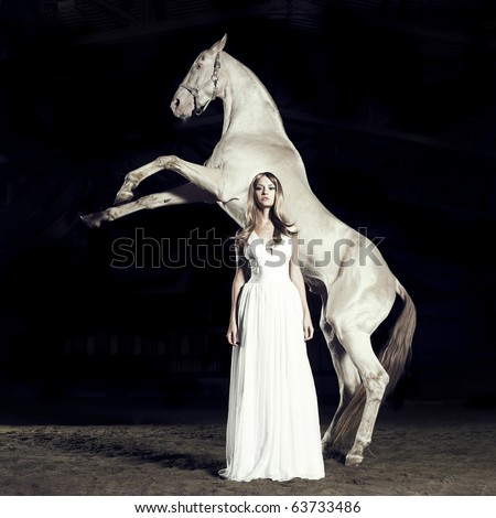 Beautiful blonde in white dress and white horse in rack - stock photo