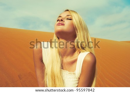Beautiful blonde in white dress in orange desert. UAE - stock photo