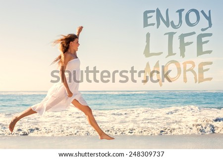 Beautiful blonde in white sundress jumping up on the beach against enjoy life more - stock photo