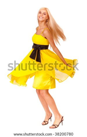 Beautiful blonde in yellow dress with black belt is joyfully turned, it is isolated on white background. - stock photo