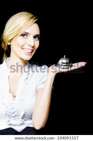 Beautiful blonde lady holding a silver service bell in her hand epitomising the old adage of 'Service With A Smile' - stock photo