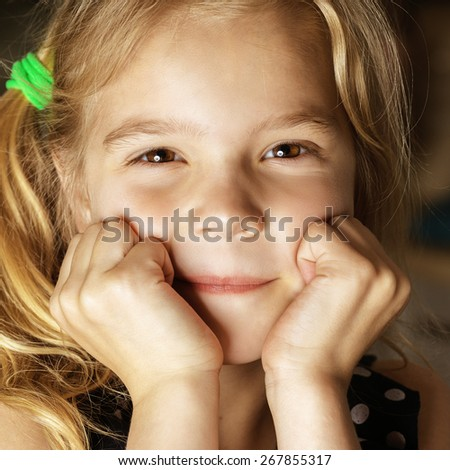 Beautiful blonde little girl sitting at table and smiling. - stock photo