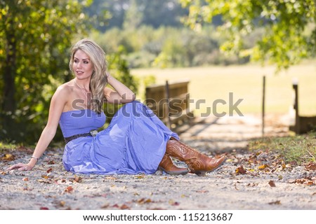 Beautiful blonde model posing in a field on a sunny day - stock photo