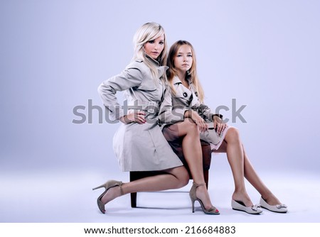 Beautiful blonde mother posing with her daughter in studio, wearing fashionable coats and looking at camera. - stock photo