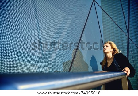 Beautiful blonde near a modern building from glass - stock photo