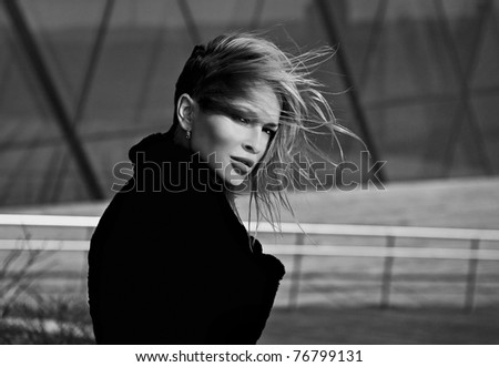 Beautiful blonde near a modern building from glass. Black-white photo. - stock photo