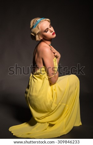 Beautiful blonde on a black background. A model posing in a beautiful dress. Beautiful jewelry and dress. - stock photo
