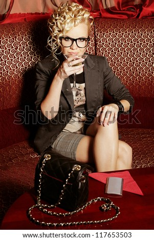 beautiful blonde party girl drinking martini on the red sofa in the club. Indoor shot - stock photo