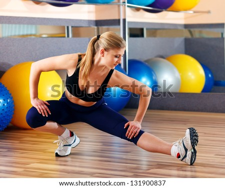 beautiful blonde performs exercises in sports hall - stock photo