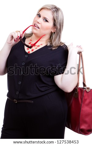 Beautiful blonde plus size woman, a model, wearing black and with dark red accessories and holding a bag and generic sunglasses. - stock photo