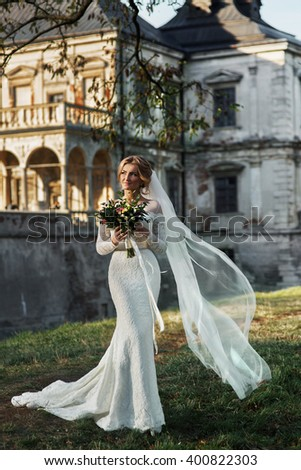 Beautiful blonde princess bride posing near old medieval castle - stock photo