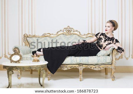 Beautiful blonde royal woman laying on a retro sofa in gorgeous luxury dress. Indoor. Copy Space - stock photo