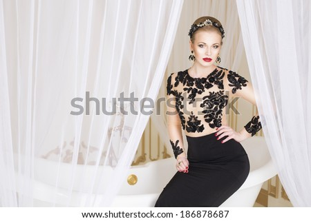 Beautiful blonde royal woman sitting on a bathtub with a tulle on it in gorgeous luxury dress. Indoor. Copy Space - stock photo