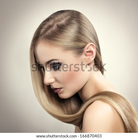 Beautiful blonde salon model with professional make-up and long straight hairstyle. Young pretty Caucasian woman with shiny healthy hair. - stock photo