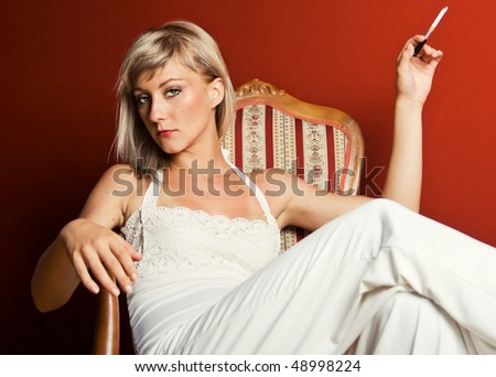 Beautiful blonde sitting in a vintage chair holding a cigarette - stock photo