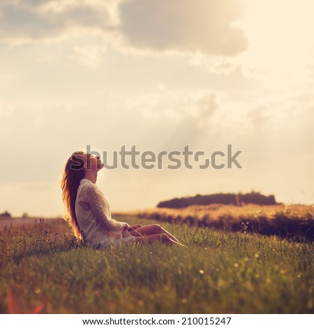 beautiful blonde sitting on a sunset - stock photo