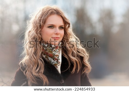 beautiful  blonde  smiling  women  in brown  coat and neckerchief have wonderful  eyes and lips in winter background  - stock photo