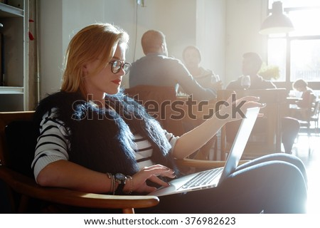 Beautiful blonde student working at a coffee shop with a laptop. female freelancer connecting to internet via computer. flare light - stock photo