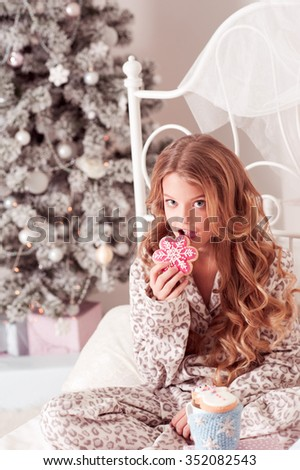 Beautiful blonde teen girl 8-10 year old biting gingerbread, drinking tea, sitting in bed in room over Christmas tree. Celebration. Christmas eve. Looking at camera.  - stock photo