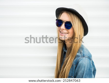 Beautiful blonde, trendy girl with sunglasses and hat is posing on white background. - stock photo