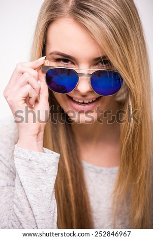 Beautiful blonde, trendy girl with sunglasses is smiling and looking at the camera. - stock photo