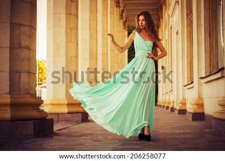 Beautiful blonde with a long curly hair in a long evening dress in motion outdoors near retro vintage building in summer sunset. Copy Space - stock photo