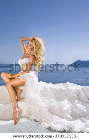 beautiful blonde with long hair bride in amazing pink wedding dress with a long train and roses sitting on a view of the island of Santorini in Greece for our honeymoon - stock photo
