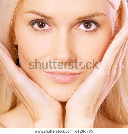 Beautiful blonde with palms at face, square. - stock photo