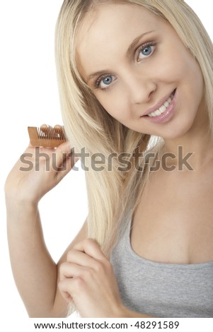 Beautiful blonde woman brushing her hair - stock photo