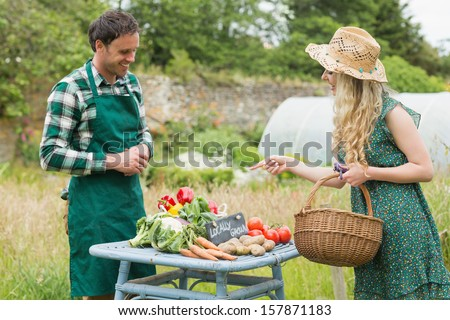 Beautiful blonde woman buying vegetables at farmers market from a handsome farmer - stock photo