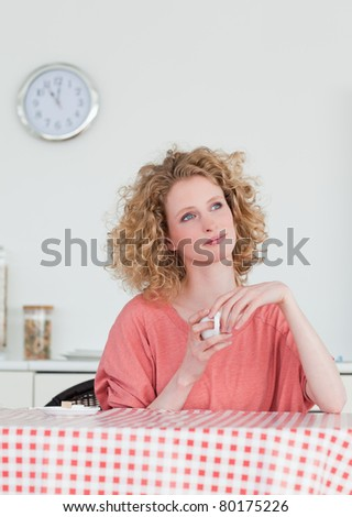 Beautiful blonde woman drinking a cup of coffee while sitting in the kitchen in her apartment - stock photo