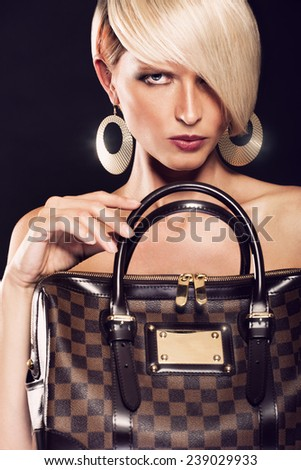 Beautiful blonde woman holding a luxury bag - stock photo
