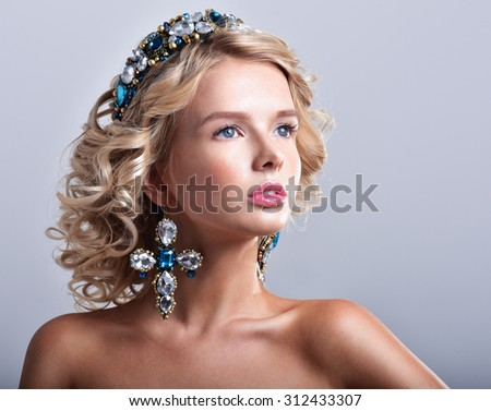 Beautiful blonde woman in a luxurious tiara and earrings. Diadem with Jewels. - stock photo