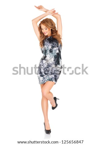 Beautiful blonde woman in a trendy dress and high heels dancing with her arms raised above her head and foot in the air isolated on white - stock photo