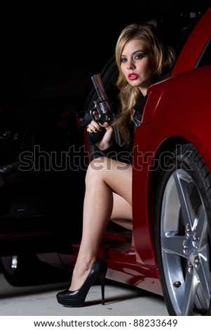 Beautiful Blonde Woman in her twenties holding a gun siting in a car. Shot at night with Strobes for shadowing effect. - stock photo