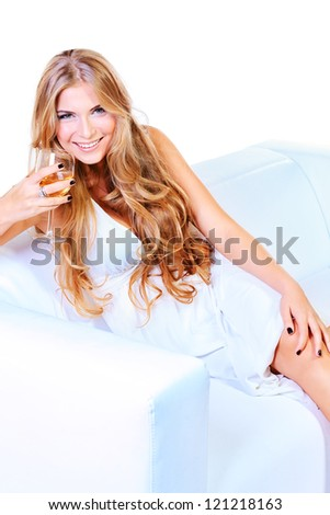 Beautiful blonde woman in light white dress sitting on a sofa. Isolated over white. - stock photo