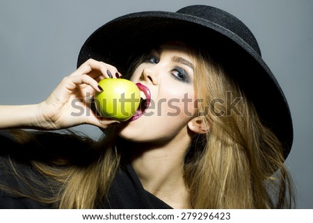 Beautiful blonde woman in retro black hat with bright make up biting fresh green apple standing on gray background copyspace, horizontal picture - stock photo