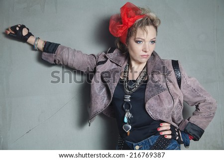 Beautiful blonde woman in rock style stands near concrete wall with a raised hand - stock photo
