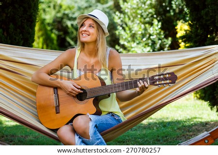 Beautiful blonde woman is sitting on hammock and playing her guitar.Playing guitar   - stock photo