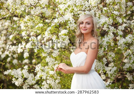 beautiful blonde woman portrait in a flowered spring garden - stock photo
