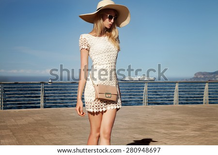 Beautiful blonde woman posing in harbor at sunny summer day. Girl wearing fashionable sunglasses . - stock photo