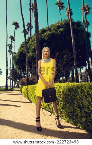 beautiful blonde woman posing with handbag in yellow dress among palm trees. Fashion photo - stock photo