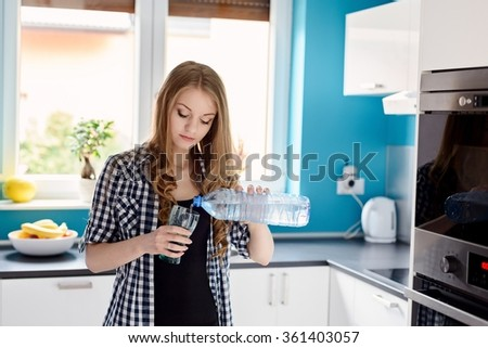 Beautiful blonde woman pouring water from a bottle into a glass. Standing in the kitchen. Dressed in a plaid shirt.  - stock photo
