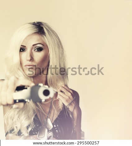Beautiful blonde woman  shooting gun - stock photo